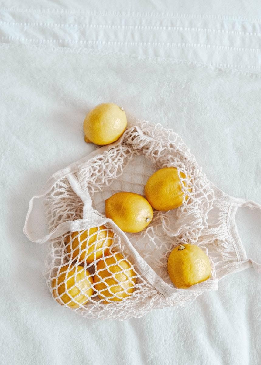 Image of a bag of lemons. Seasonal self-care ideas. Make lemonade to enjoy during the hot summer days outside.