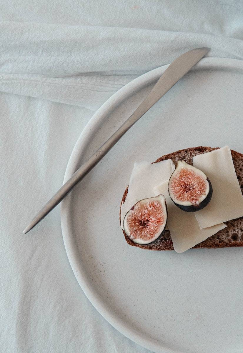 Image is purely for decorative purposes only. Featuring a fig on top of a slice of rye bread this is the anti the clean eating trend which is popular in the wellness industry