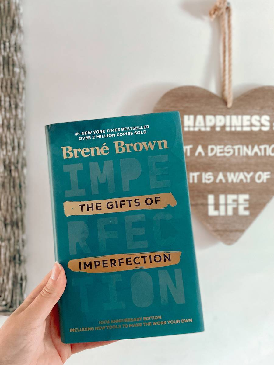 The Gifts of Imperfection hardback book cover. Turquoise, gold lettering. A wooden heart picture can be seen in the background saying happiness is not a destination, it's a way of life